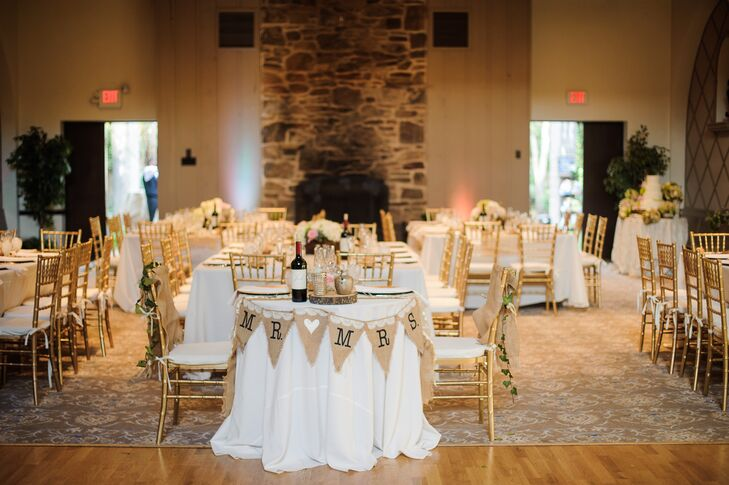"""Sarah and Tom made their sweetheart table stand out with a few rustic details. A sweet burlap and lace pennant banner surrounded the table with """"Mr. [heart] Mrs."""" Burlap and ivy chair sashes as well as a wooden centerpiece base further highlighted their seating."""