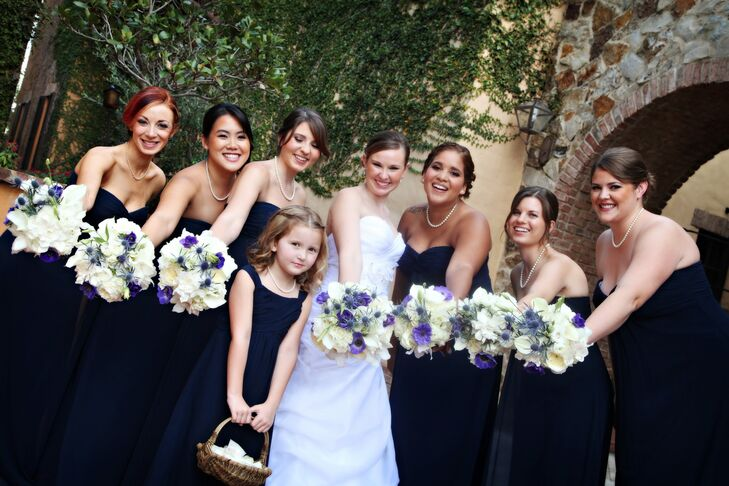 Staci's bridesmaids wore simple long strapless dresses in navy blue from Bill Levkoff. They accessorized with pearl necklaces and elegant updo hairstyles.