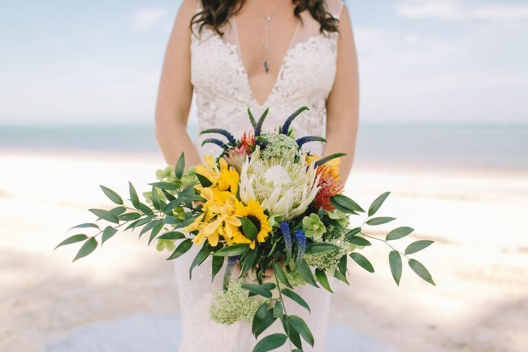 Bride holding sunflower bouquet on beach