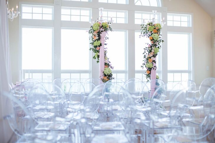 Ryan and Brian exchanged vows in the penthouse of the beachfront estate. They loved the oversize windows and amazing vistas of the ocean and dunes. Wedding planner Glam and Lace and florist Renee Landry Events worked together to set up two blush pillars, which they wrapped with peach and green flowers.