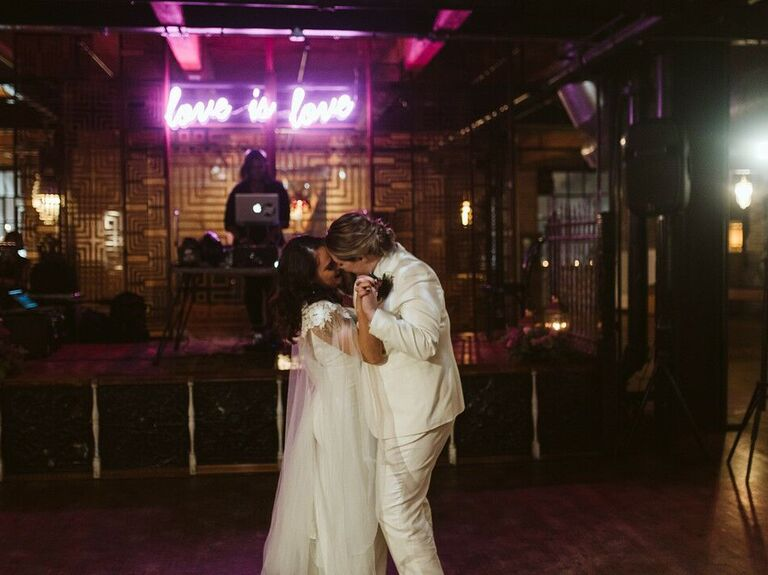 Couple slow dancing in front of neon sign