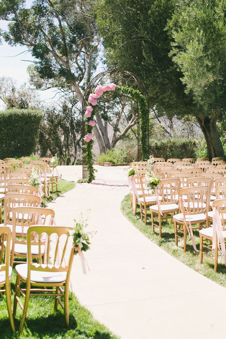 The couple held their ceremony outside at Ahmanson Ranch in Calabasas, California, where gold chairs were arranged in rows for guests to sit and watch the service. The wedding arch where vows were said was covered in greenery accented with pink hydrangeas.