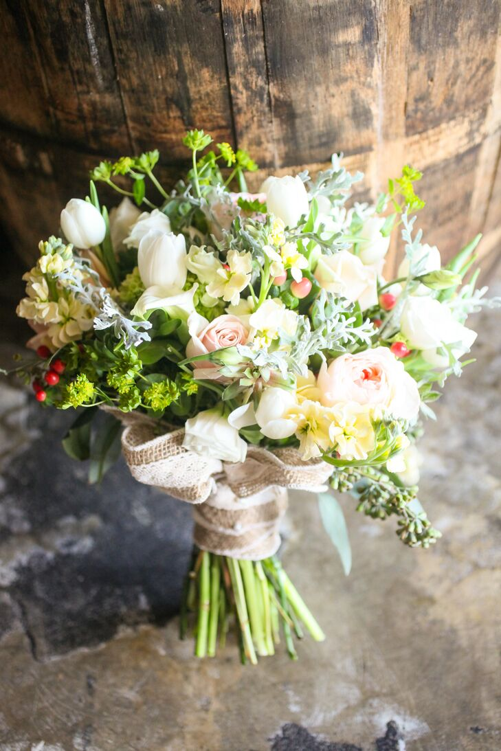 """""""The flowers absolutely brought the whole wedding together,"""" says Chelsea. She carried a bouquet of white tulips, blush roses, blush peonies, yellow orchids, white roses and red hypericum berries down the aisle. It was arranged by Redman Steele Floral Design Studio."""