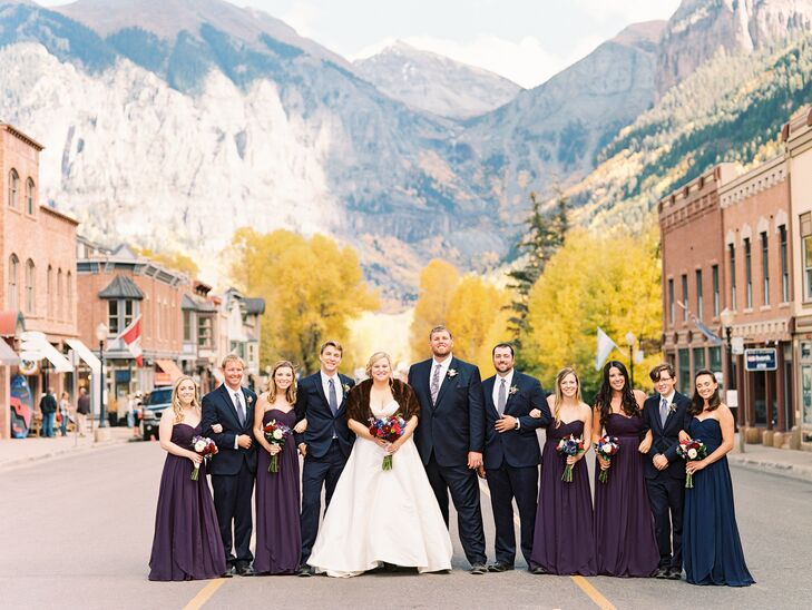 The fall-inspired palette—violet, navy, cranberry and green—bridesmaids wore dark purple strapless gowns while groomsmen sported deep navy suits with striped ties.