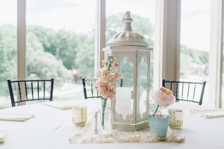 Small, simple flower arrangements and small votive candles were displayed next to cream lanterns for the simple and elegant centerpiece decor.