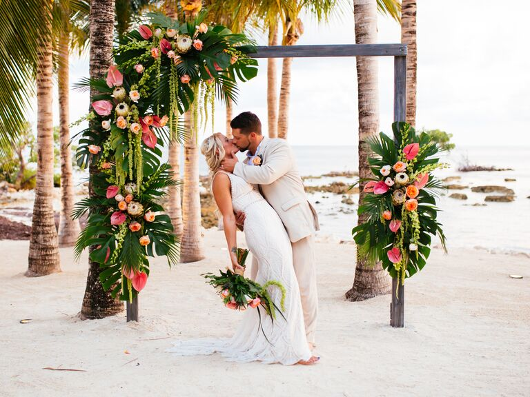 married couple kissing during a beach wedding ceremony