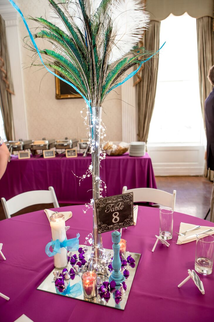Because Amber didn't want flower arrangements as her centerpieces, her mother went the DIY route without using flowers. She arranged ostrich and peacock feathers in tall, skinny vases and  then wrapped each one in lights. The arrangements were placed on mirrors at each table. We love that they chose bright purple tablecloths to contrast with the feather centerpieces.