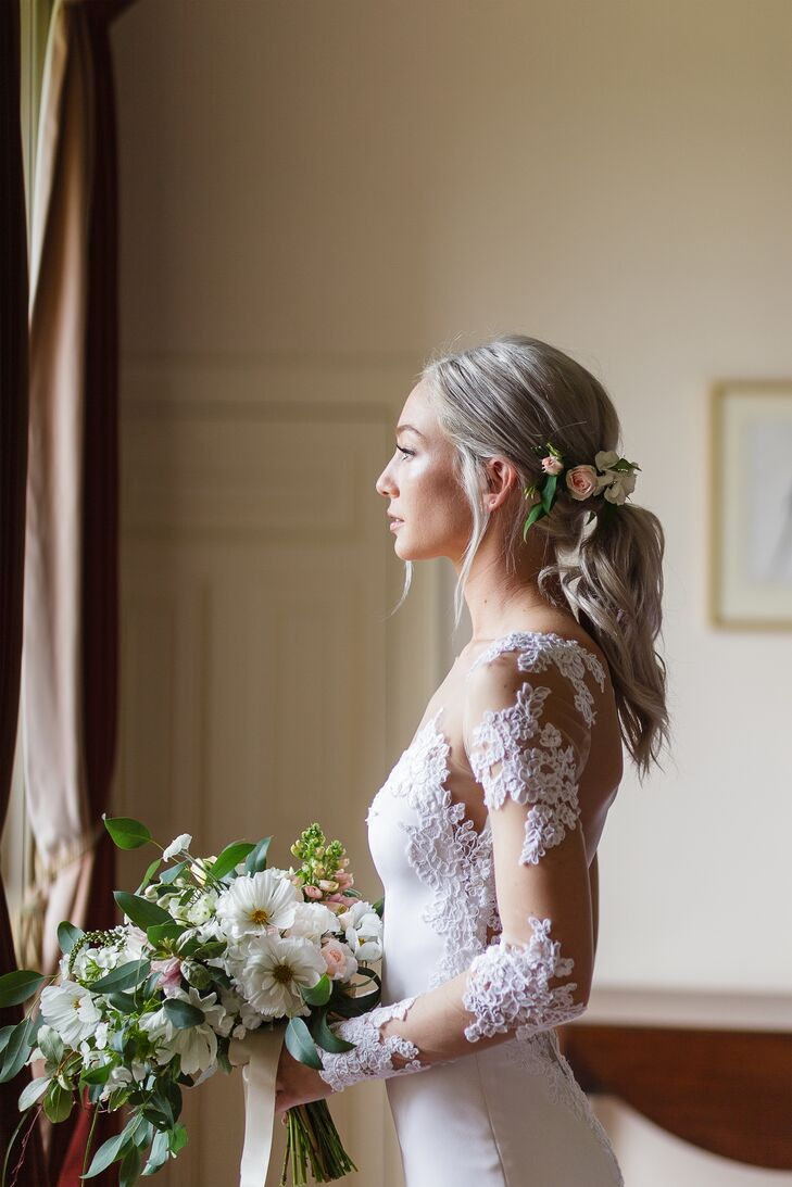 Bringing a bohemian quality to her modern, romantic wedding gown, Elizabeth wore her hair in a low ponytail. Loose, face-framing tendrils and elegantly undone waves lent a softness to her look. A cluster of small pink and cream-colored roses were added at the base of the ponytail, capturing the essence of the Irish countryside and the beauty of the garden where the ceremony took place.