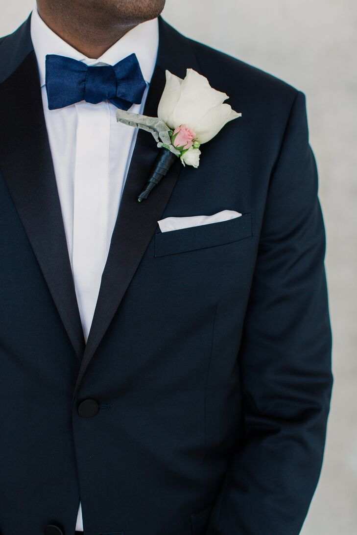 Instead of choosing a classic black tuxedo, Andrew brought out his personality a bit more with a dapper, midnight navy one by Theory. A white shirt and navy bow tie only enhanced his look. The color contrast also made his grand white rose, pink rose and dusty miller boutonniere from the Flower Bazaar stand out that much more.