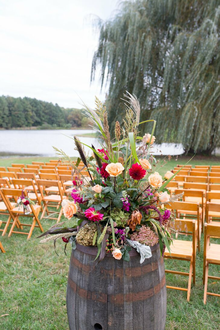 Wine-barrel flower arrangements at the ceremony included peach roses, burgundy dahlias, dried hydrangeas, dusty miller, hypericum and other wildflowers.