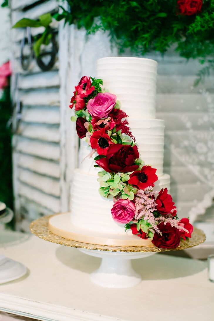Simon Lee Bakery created this beautiful three-tier cake frosted in white buttercream. A cascade of roses, anemones, astilbes, garden roses and antique hydrangeas added a pop of color to the display.