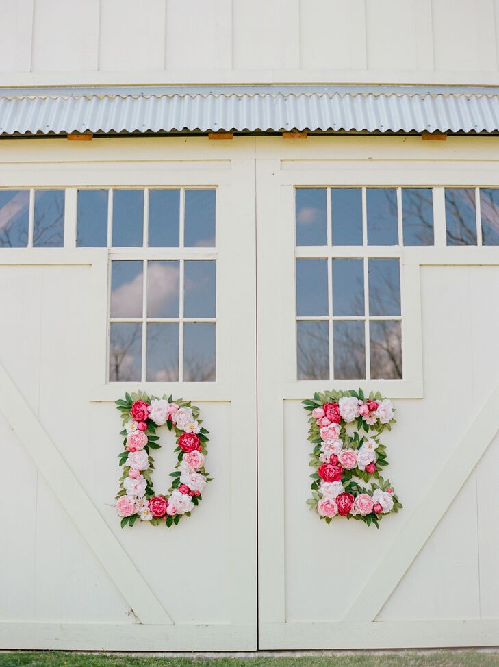 """""""A large focus of our wedding was florals, so I picked flowers with many shades of pink,"""" Deborah says. These monogram letters were crafted by Houston's Flower Vibes and hung on the doors of the barn at Chandelier Grove in Tomball, Texas, where the reception was held."""