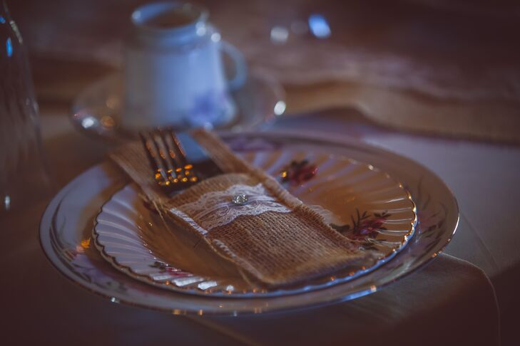 Floral-print, antique china added a vintage touch to each place setting while burlap utensil holders lent a rustic element to the setup.