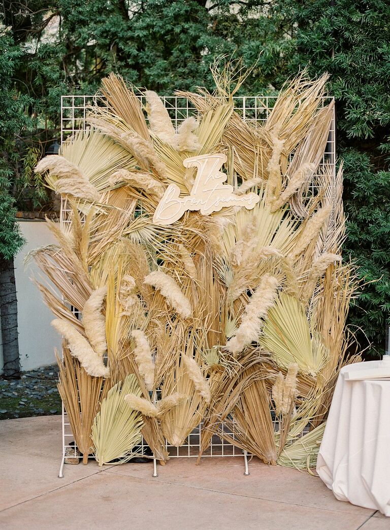 Decorative wall with dried grasses and custom sign