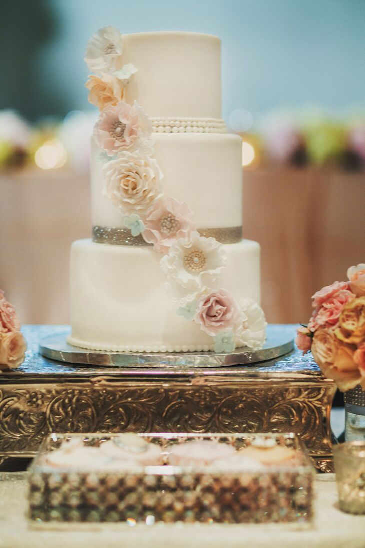 Pink and white sugar roses cascaded down the layers of the three-tier white wedding cake.