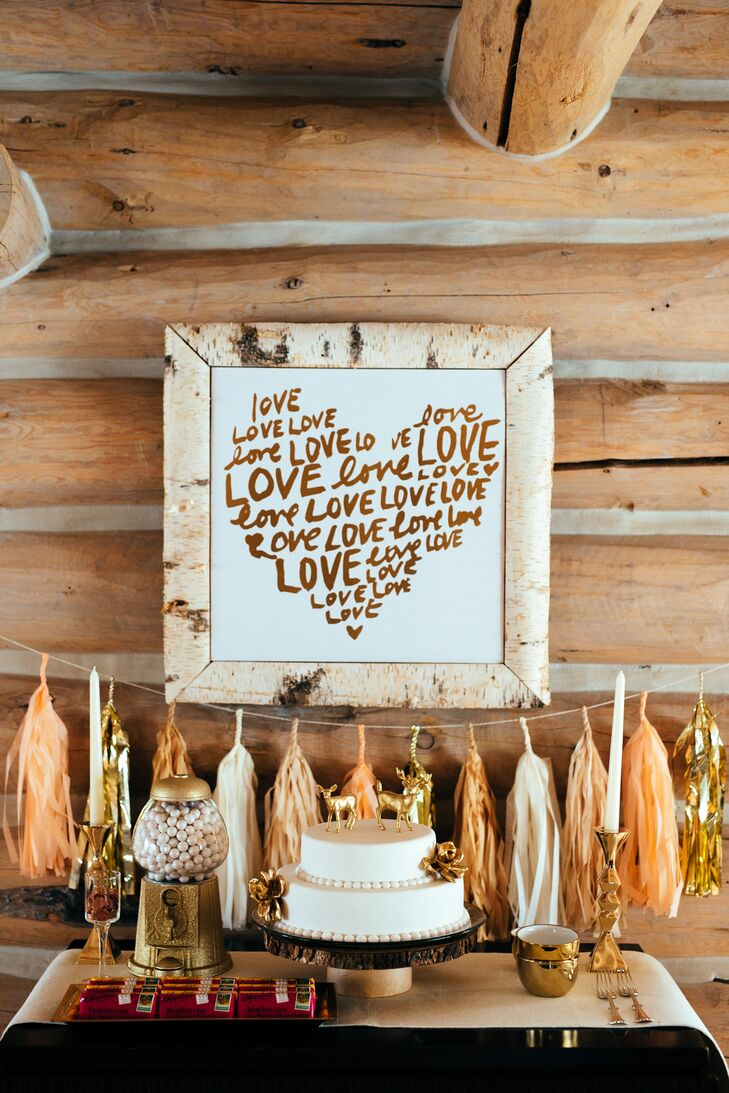 "Suzi's father handmade a Michigan birch tree picture frame to put around a white and gold canvas print that repeated the word ""love"" in the shape of a heart. The decoration hung over the cake table along with peach and gold tassels for a whimsical look that we can't help but love."