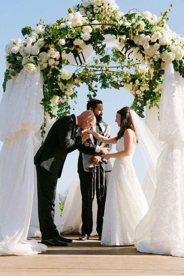 Alyssa and Alex got married under a chuppah adorned with ivory blooms and greenery at the top, and thick white sheets covering the sides.