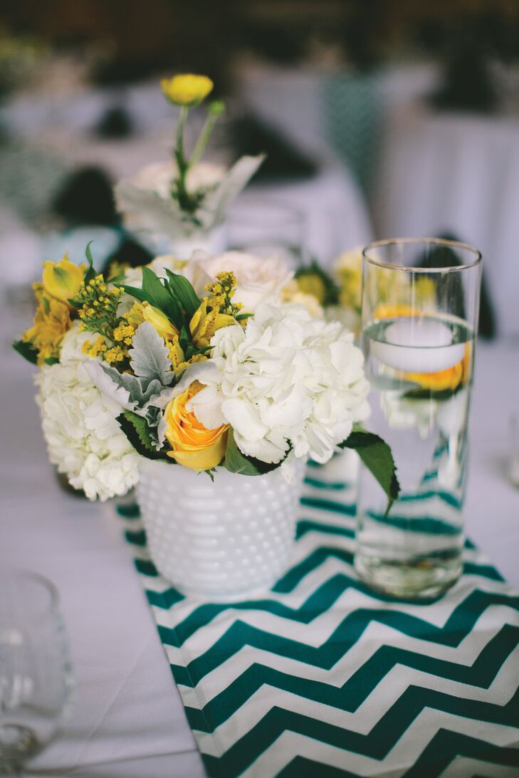 Sayo and Blake decorated the reception tables with milk glass, swiss dotted vases filled with white hydrangeas, yellow roses and lamb's ear. The couple wanted white and yellow flowers in honor of their spring wedding. They added teal and ivory chevron runners to each table to match the color palette.