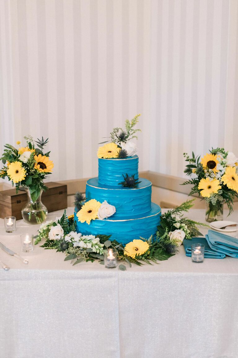 Bright blue cake decorated with yellow daisies and sunflowers