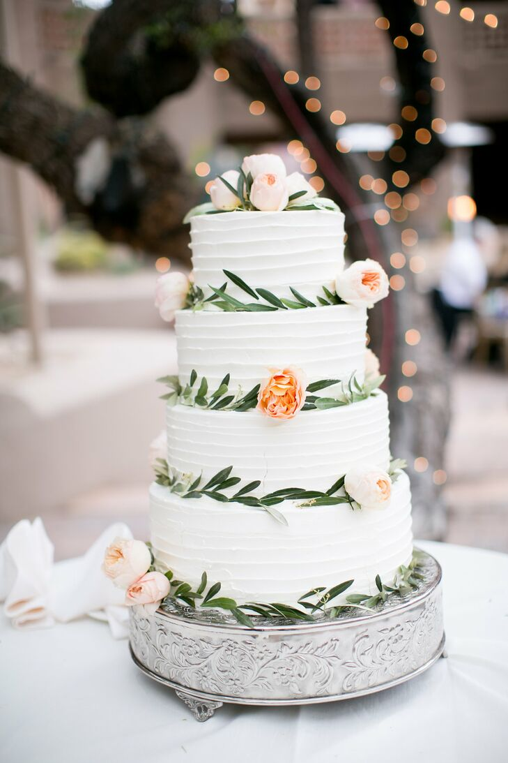 The couple's four-tier wedding cake was prepared by their venue, Boulders Resort & Spa in Carefree, Arizona. It featured blush and light orange florals and greenery. The white cake with a berry and custard filling sat atop a floral printed stand.