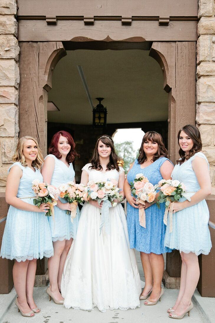 The bridesmaids wore knee-length eyelet lace dresses in baby blue; the maid of honor wore a darker shade of blue. Color and visual interest was added with slim gold belts and gold flats.