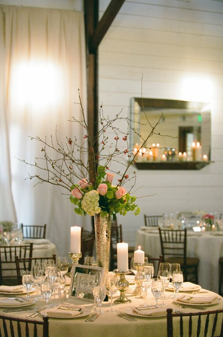 Tall gold vases held a small arrangement of hydrangeas, roses, branches and other greenery, giving the tables an elegant rustic look.