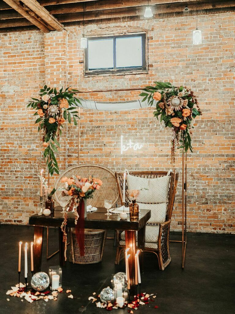 Modern rustic sweetheart table at wedding reception with neon sign, floral arrangements and candles on the floor with disco balls