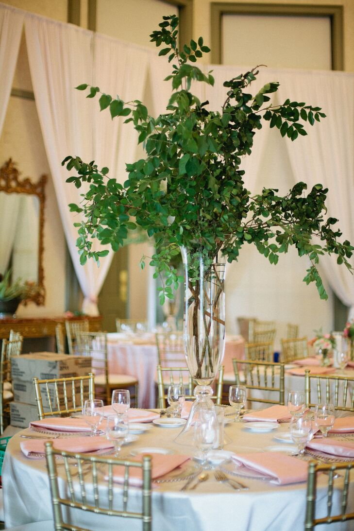 The head table was decorated with a garland of sprengeri ferns, nagi, plumose, magnolia leaves and pink and coral blooms, while round dining tables were accented with tall vases filled with leafy branches.