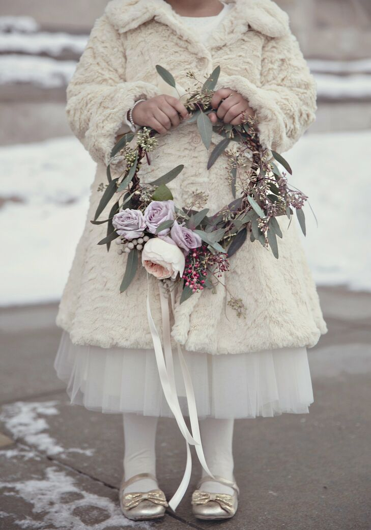 The three flower girls wore matching ivory fur coats and carried wreaths made of fresh eucalyptus, garden roses and silver spray roses.