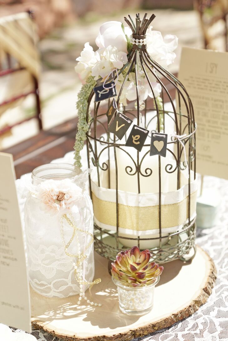 """The dining table centerpieces were totally DIY by Ashlee and her mom. They included a mix of vintage decor, including lace-wrapped mason jars, glasses, cages and wooden slabs mixed with succulents and flowers. Many decorations continued a """"love"""" motif."""