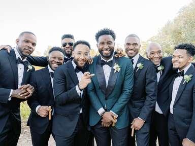 Groom posing with groomsmen on wedding day