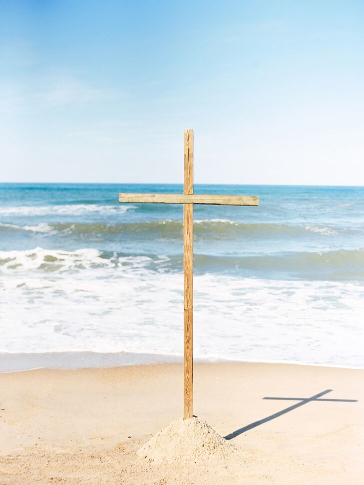 """""""We designed the ceremony to be very simple with minimal decor, to keep the focus on our coming together as husband and wife before God,"""" Taylor says. They had their ceremony at low tide, and at the front, next to the water, they displayed a large reclaimed-wood cross made by Taylor's grandfather."""