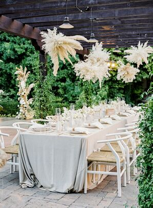 Boho Reception Table With Pampas Grass Chandeliers and White Wishbone Chairs