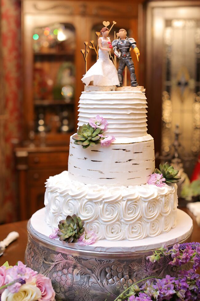 The wedding cake really showed off the couple's whimsical side. The round almond cake featured a bottom tier covered in rosettes, a center tier textured to look like aspen wood and the top tier ruffled, with a video-game-inspired topper customized for the bride and groom.