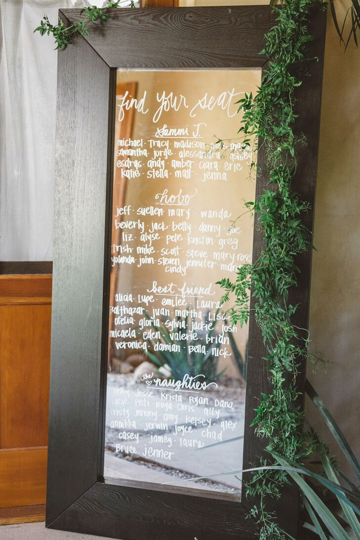 "At the reception, guests located their seating assignments on a tall wood-framed mirror. ""One of my favorite details was the seating chart on an oversize mirror,"" Tracy says. The chart was made by the event's planner, Katie Seefeldt of Wedding Kate."