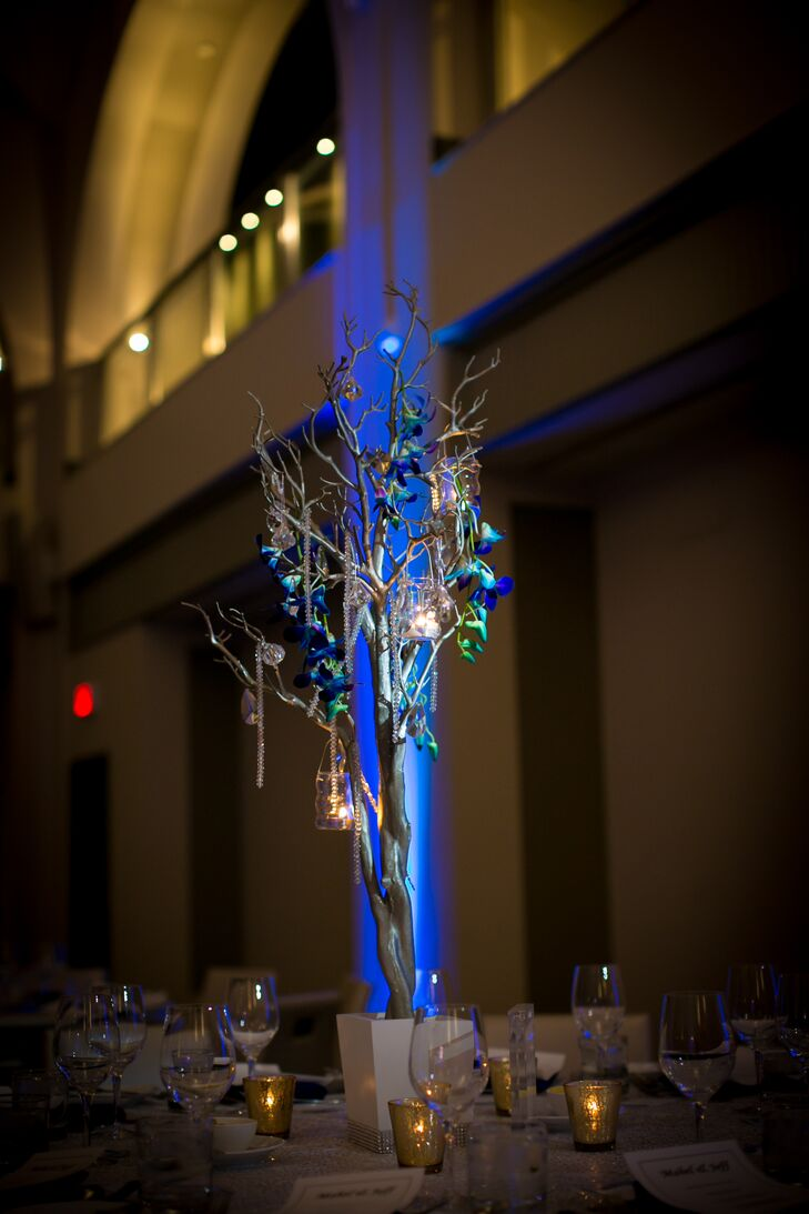For the winter, modern centerpiece decor, OMG Events covered small winter trees with blue orchids, crystals, and candles for the reception at Arcadian Court in Toronto, Ontario.