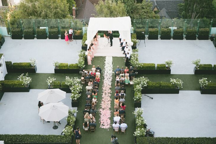 Making the most of The London's many stunning event spaces, Jocelyne and Nick began the day in Hampton Court, a rooftop rose garden overlooking West Hollywood toward Los Angeles. The pair kept the affair intimate, gathering together their closest family members and friends. Two by two, chiavari chairs framed the aisle and romantic rose petals lined the aisle, creating a whimsical ombre effect, leading to an airy wedding arch where Jocelyne and Nick exchanged vows.