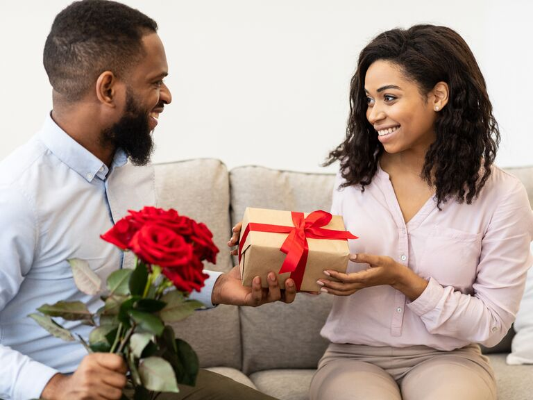 Couple exchanging gift and flowers