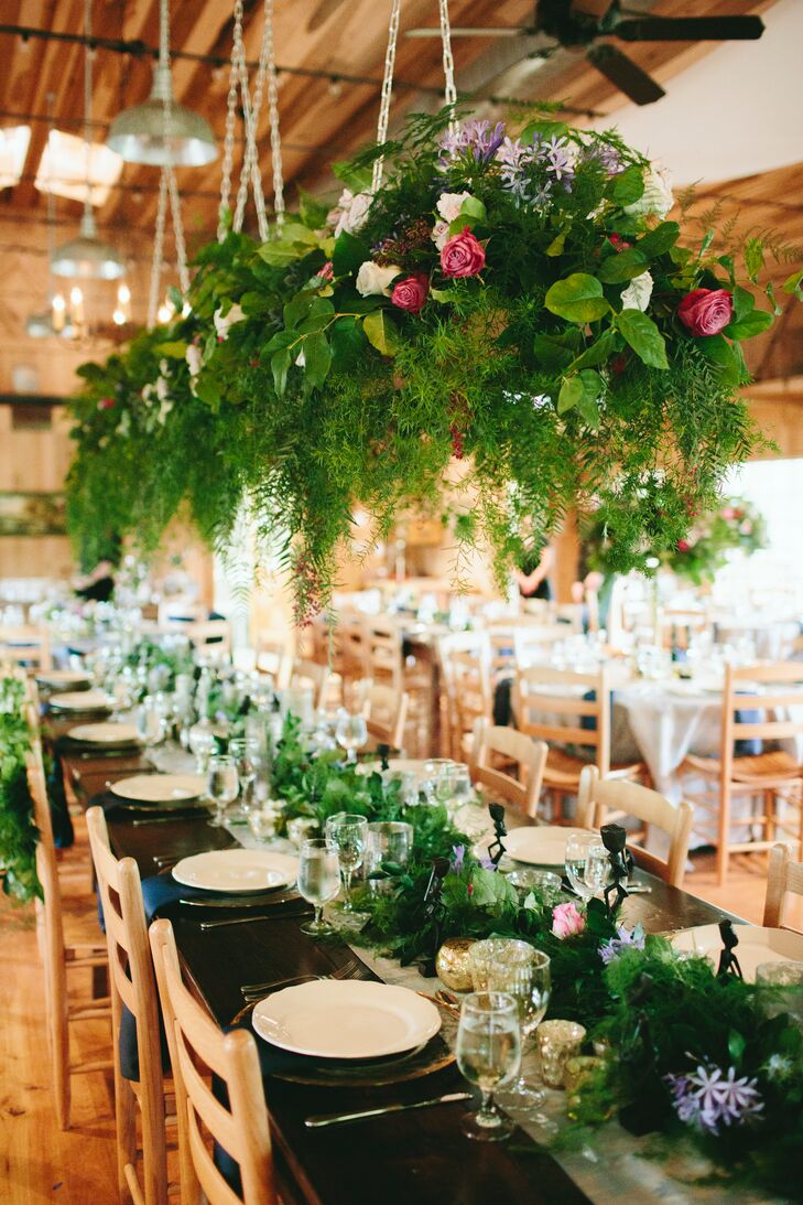Tyler and Lissa of Flora crafted greenery-rich centerpieces and a long, hanging garland display over the long banquet table at Yesterday Spaces in Leicester, North Carolina.