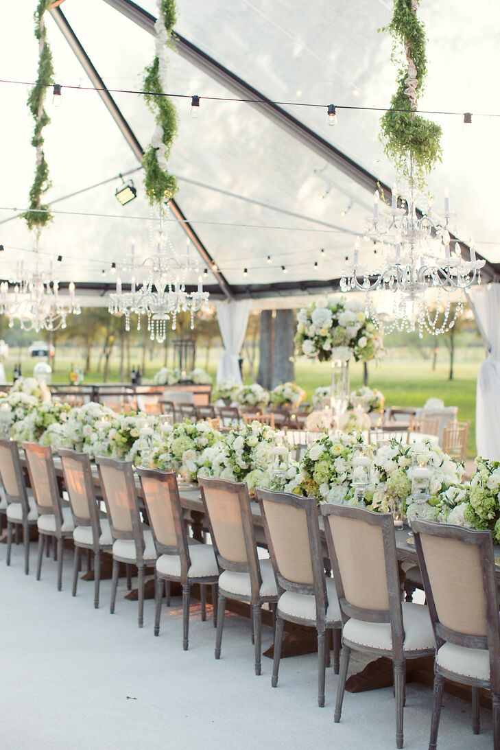 Bella Flora created a bold white and green floral head table runner to channel Lucy and Will's natural wedding theme. Hanging crystal chandeliers with cascading greenery added to the elegance.