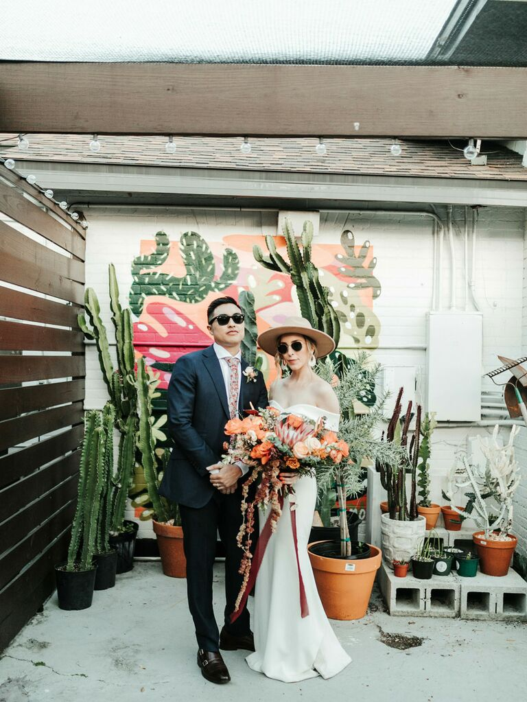 Boho bride and groom posing in front of succulents
