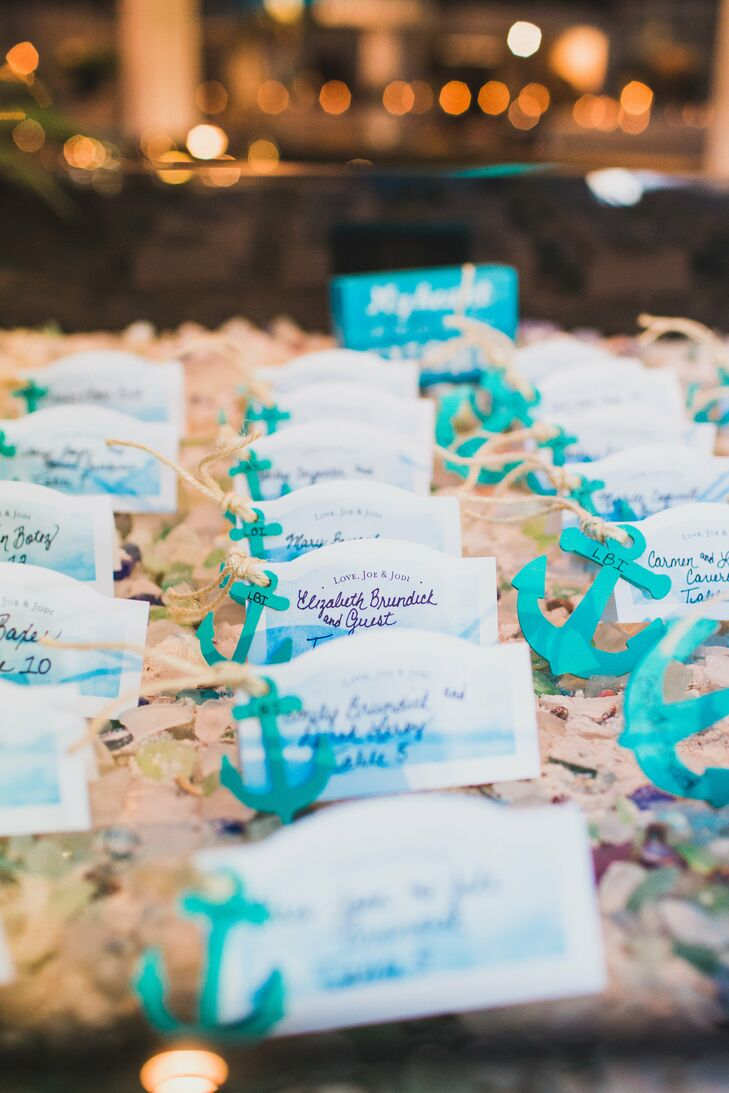 Jodi and Joe's nautical theme became more prominent as all 140 guests entered the reception. Each wave-inspired escort card had an aqua anchor tucked into the side. The notes stood out among a bed of sand, sea glass and seashells for a more literal take on their nautical inspiration.