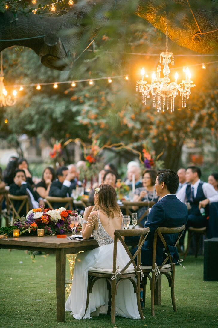"""""""To go along with the elegant chandeliers, we added touches of gold in brass candleholders and chargers,"""" Lisa says. """"We truly felt that this wedding was going to be a dream come true, and it was. It was the epitome of rustic elegance."""""""