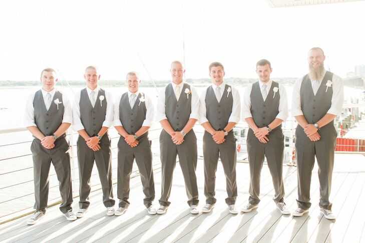 The groomsmen wore formal gray vests and slacks with Chuck Taylors. They also wore white rose boutonnieres.