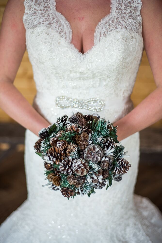 """Blair held a winter bouquet filled with brown pinecones and evergreen plants, all of which was frosted on top. """"There were no flowers in our wedding,"""" Blair says. """"Instead, we used pinecone and evergreen bouquets and boutonnieres to keep with our woodsy theme!"""""""