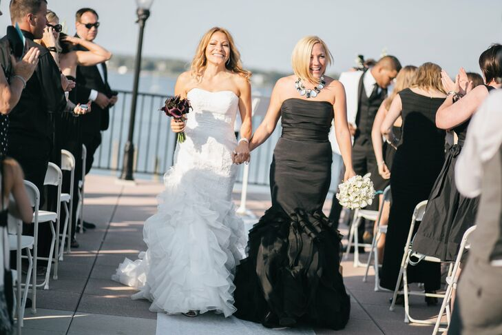 To go with their modern black and white theme, the couple decided to wear black and white gowns. Ashley went with a black Vera Wang mermaid gown and a black and white statement necklace that complemented Gabby's dress as well as the day's theme. Gabby wore a trumpet gown by Galina Signature with lace appliques and organza ruffle skirt.