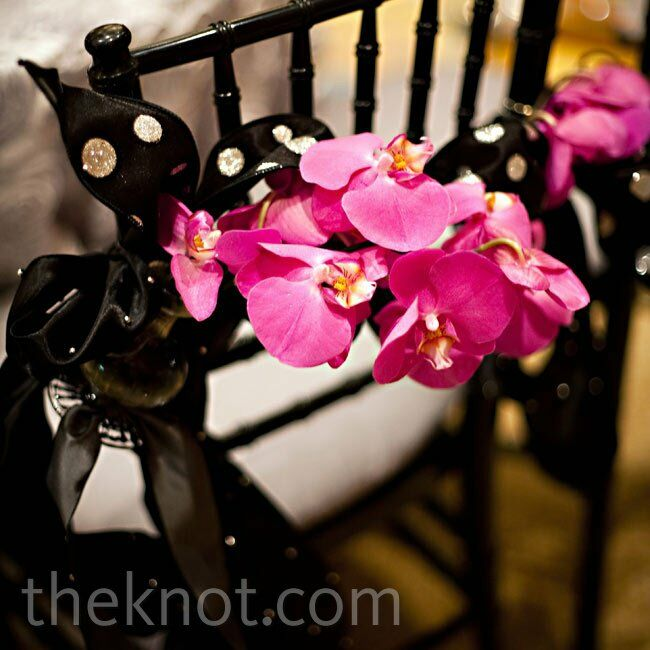 A cluster of blooms tied with black dotted ribbon marked the newlyweds' reception seats.