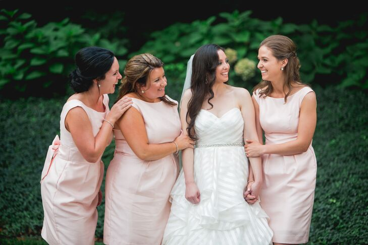 "Elon stood in her ivory wedding dress with a sweetheart neckline next to her bridesmaids, who wore light pink dresses in the same style. ""For the bridesmaids, we wanted a classy feel,"" the couple says. ""We chose a Jenny Yoo gown with classic lines in a soft pink."""