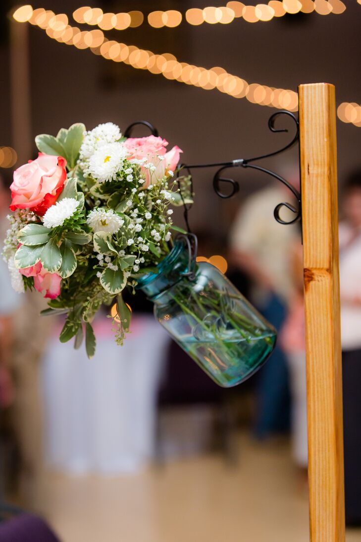 """""""Roses, coffee bean pods, peonies, baby's breath, and green filler were held in blue glass mason jars that came from Micaela's great grandmother,"""" says the couple."""