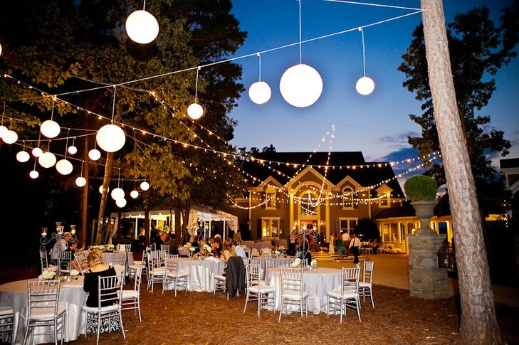 White tables and chairs were placed around the property along with white lanterns hanging over the pool and in the trees.